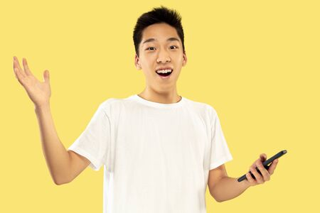 Korean young mans half-length portrait on yellow studio background. Male model in white shirt. Using smartphone for betting, news reading or talking. Concept of human emotions, facial expression. 写真素材