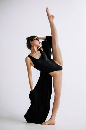 Fashion ballet. Young female ballet dancer in black bodysuit against white studio background. Asian ballerina like a fashion model. Style, contemporary choreography concept. Creative art photo. 免版税图像