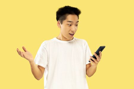 Korean young mans half-length portrait on yellow studio background. Male model in white shirt. Using smartphone for betting, news reading or talking. Concept of human emotions, facial expression. Stok Fotoğraf