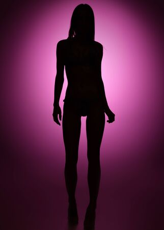 Full-length fit and thin female silhouette on dark purple background. Party disco vibes. Woman in fashionable bodysuits posing. Creative art style. Concept of fashion, beauty, club or party.