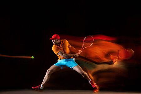 Un uomo caucasico che gioca a tennis isolato su sfondo nero in condizioni di luce mista. Studio shot di un giovane giocatore maschio in forma in movimento o in azione durante il gioco sportivo. Concetto di movimento, sport, stile di vita sano. Archivio Fotografico