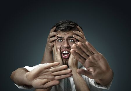 A male model surrounded by hands like his own thoughts on dark background. A young man doubts, cant choose the right decision and decide. Concept of mental problems, troubles in work, indecision.