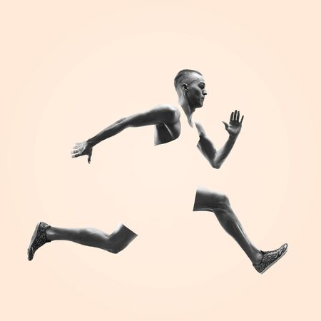 Young caucasian man running isolated on studio background. One male runner or jogger. Healthy lifestyle, movement, action, motion, advertising and sports concept. Abstract design. Stockfoto