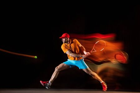 One caucasian man playing tennis isolated on black background in mixed light. Studio shot of fit young male player in motion or action during sport game. Concept of movement, sport, healthy lifestyle.