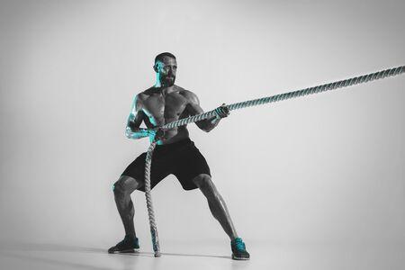 Comparación de fuerzas. Entrenamiento culturista caucásico joven sobre fondo de estudio en luz de neón. Modelo masculino musculoso con la cuerda. Concepto de deporte, culturismo, estilo de vida saludable, movimiento y acción. Foto de archivo