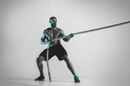 Comparison of forces. Young caucasian bodybuilder training over studio background in neon light. Muscular male model with the rope. Concept of sport, bodybuilding, healthy lifestyle, motion and action. Archivio Fotografico