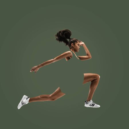Young african woman running isolated on green studio background. One female runner or jogger. Silhouette of jogging athlete. Concept of healthy lifestyle, sport, movement, action. Abstract design.