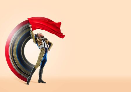 One caucasian toreador isolated on yellow studio background. Studio shot of torero or bullfighter in motion or movement. Negative space. Concept of movement and action. Abstract design.