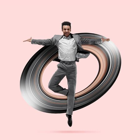 One african ballet dancer isolated on coral studio background. Studio shot of businessman in motion or movement. Dancing office worker. Concept of movement and action. Abstract design.
