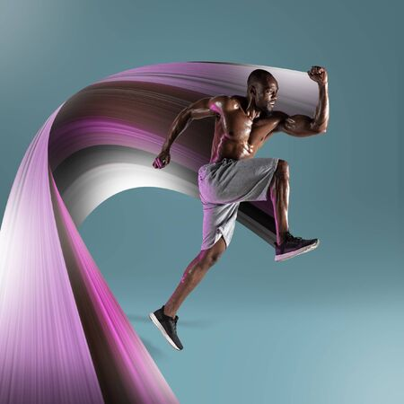 Young african-american athlete training on blue studio background. Muscular male model jumping. Concept of sport, bodybuilding, healthy lifestyle, movement, action. Abstract design.