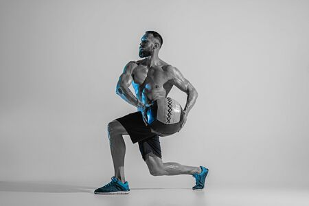 Making a choice. Young caucasian bodybuilder training over studio background in neon light. Muscular male model with the ball. Concept of sport, bodybuilding, healthy lifestyle, motion and action.