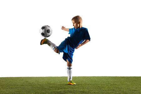 Young boy as a soccer or football player in sportwear making a feint or a kick with the ball for a goal on white studio background. Fit playing boy in action, movement, motion at game.