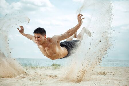 Weightless. Young healthy man athlete doing exercise at the beach. Signle male model shirtless training air at the river side in sunny day. Concept of healthy lifestyle, sport, fitness, bodybuilding.