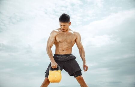 Young healthy man athlete doing exercise with the weight at the beach. Signle male model shirtless training at the river side in sunny day. Concept of healthy lifestyle, sport, fitness, bodybuilding. Foto de archivo - 124598142