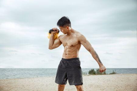 Junger gesunder Mannathlet, der Übung mit dem Gewicht am Strand tut. Signle männliches Modell mit nacktem Oberkörper Training an der Flussseite am sonnigen Tag. Konzept des gesunden Lebensstils, Sport, Fitness, Bodybuilding. Standard-Bild