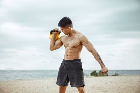Young healthy man athlete doing exercise with the weight at the beach. Signle male model shirtless training at the river side in sunny day. Concept of healthy lifestyle, sport, fitness, bodybuilding. Stock Photo