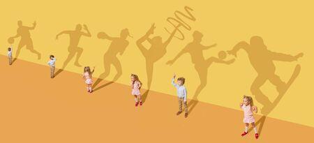 Kindheit und Traumkonzept. Begriffsbild mit Kindern und Schatten an der gelben Studiowand. Kleine Mädchen und Jungen wollen Turnerin, Tänzerin, Künstlerin, Boxerin, Läuferin oder Fußballspielerin werden.