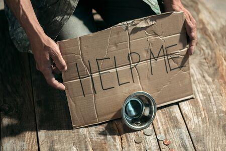 Manos de mendigo masculino en busca de dinero con el signo AYUDARME de la bondad humana en el piso de madera en la vía pública o pasarela de la calle. Pobres sin hogar en la ciudad. Problemas con las finanzas, lugar de residencia. Foto de archivo