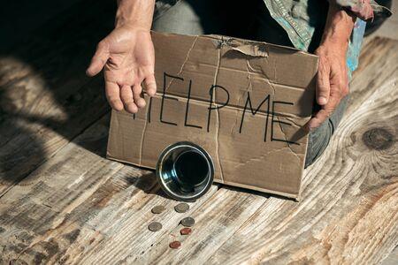 Manos de mendigo masculino en busca de dinero con el signo AYUDARME de la bondad humana en el piso de madera en la vía pública o pasarela de la calle. Pobres sin hogar en la ciudad. Problemas con las finanzas, lugar de residencia.