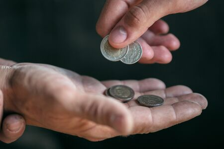Mains de mendiants masculins cherchant de l'argent, des pièces de la bonté humaine sur le plancher en bois du chemin public ou de la passerelle de la rue. Les sans-abri pauvres dans la ville. Problèmes financiers, lieu de résidence. Banque d'images