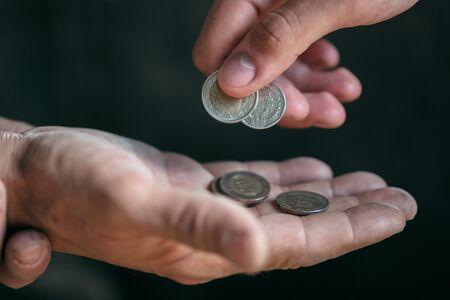 Mannelijke bedelaarshanden op zoek naar geld, munten van menselijke vriendelijkheid op de houten vloer op het openbare pad of straatpad. Dakloze armen in de stad. Problemen met financiën, woonplaats. Stockfoto