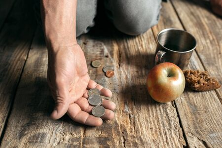 Male beggar hands seeking food or money with coins tin from human kindness on the wooden floor at public path way, street walkway. Homeless poor in the city. Problems with finance, place of residence.