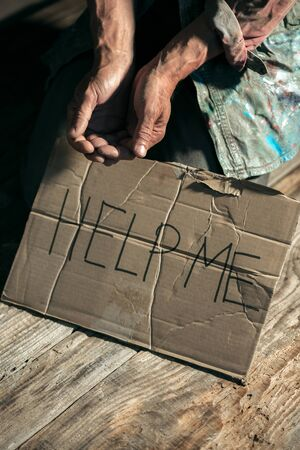 Male beggar hands seeking money with sign HELP ME from human kindness on the wooden floor at public path way or street walkway. Homeless poor in the city. Problems with finance, place of residence.
