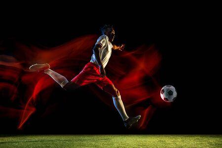 Joven jugador de fútbol o fútbol masculino afroamericano en ropa deportiva y botas pateando la pelota para el gol en luz mixta sobre fondo oscuro. Concepto de estilo de vida saludable, deporte profesional, afición.