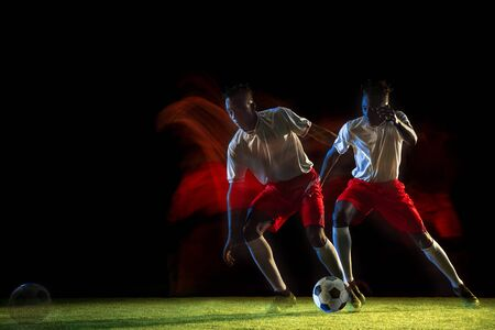 Young african-american male football or soccer player in sportwear and boots kicking ball for the goal in mixed light on dark background. Concept of healthy lifestyle, professional sport, hobby. Imagens