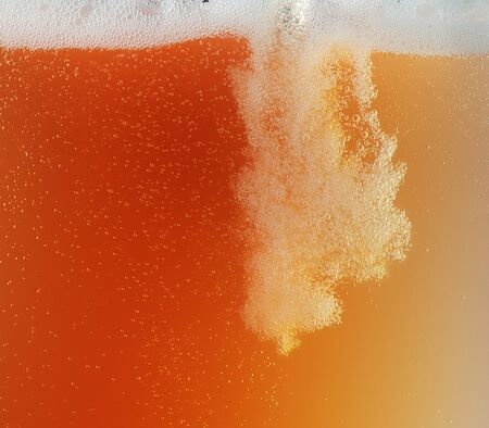 Close up view of floating bubbles in golden colored beer