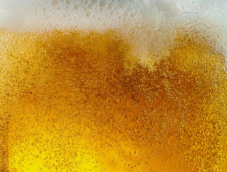 Close up view of floating bubbles in light golden colored beer Banco de Imagens