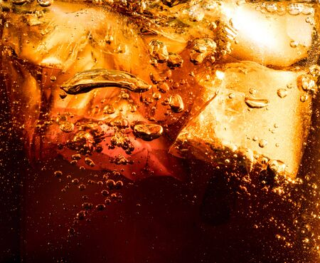 Close up view of the ice cubes in dark fizzy drink