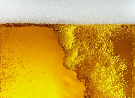 Close up view of floating bubbles in light golden colored beer Stock Photo