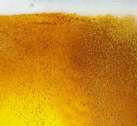 Vista ravvicinata delle bolle galleggianti nella birra di colore dorato chiaro