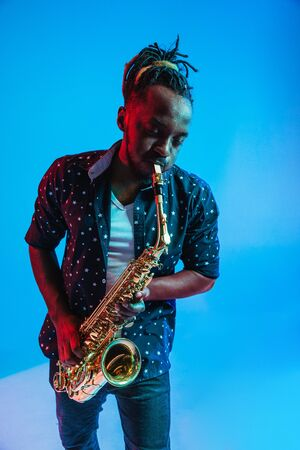 Jeune musicien de jazz afro-américain jouant du saxophone sur fond bleu studio dans un néon à la mode. Concept de musique, passe-temps. Joyeux mec attirant improvisant. Portrait coloré rétro de l'artiste.