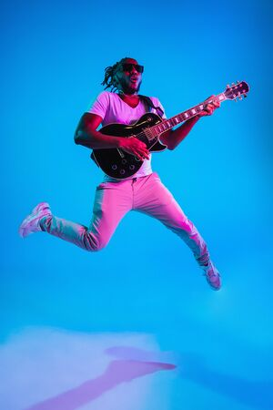 Young african-american musician playing the guitar in jump like a rockstar on blue studio background in neon light. Concept of music, hobby. Joyful attractive guy improvising. Retro colorful portrait. Stock Photo - 124767141