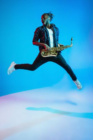 Young african-american jazz musician playing the saxophone on blue studio background in trendy neon light. Concept of music, hobby. Joyful attractive guy improvising. Retro colorful portrait of artist. Banque d'images