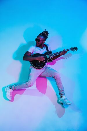Young african-american musician playing the guitar like a rockstar on blue studio background in neon light. Concept of music, hobby. Joyful attractive guy improvising. Retro colorful portrait. Reklamní fotografie