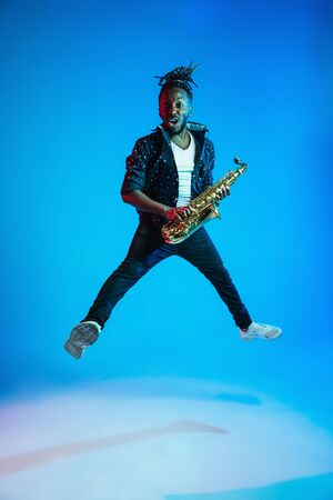 Young african-american jazz musician playing the saxophone on blue studio background in trendy neon light. Concept of music, hobby. Joyful attractive guy improvising. Retro colorful portrait of artist.