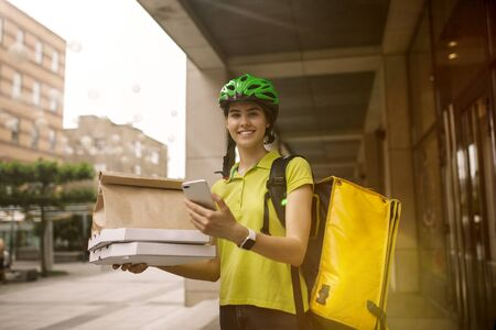 Young woman in yellow shirt delivering pizza using gadgets to track order at the citys street. Courier using online app for receiving payment and tracking shipping address. Modern technologies. Stock Photo