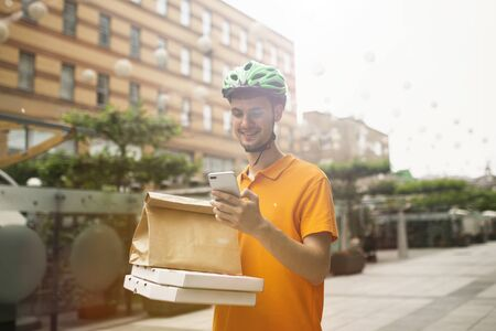 Young man in yellow shirt delivering pizza using gadgets to track order at the citys street. Courier using online app for receiving payment and tracking shipping address. Modern technologies.