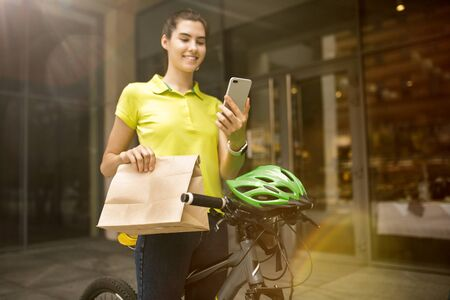 Young woman in yellow shirt delivering package using gadgets to track order at the citys street. Courier using online app for receiving payment and tracking shipping address. Modern technologies. Stock Photo