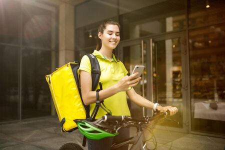Young woman in yellow shirt delivering food using gadgets to track order at the citys street. Courier using online app for receiving payment and tracking shipping address. Modern technologies.