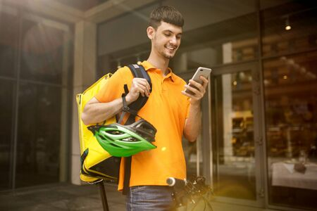 Young man in yellow shirt delivering package using gadgets to track order at the citys street. Courier using online app for receiving payment and tracking shipping address. Modern technologies.