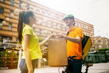 Young man in yellow shirt delivering package using gadgets to track order at the citys street. Courier using online app for receiving payment, adress and meeting the recipient. Modern technologies.