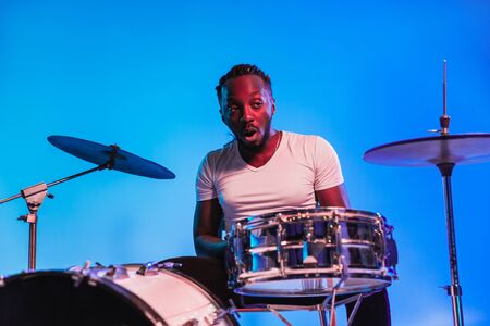 Young african-american jazz musician or drummer playing drums on blue studio background in trendy neon lights. Concept of music, hobby, inspirness. Portrait of joyful attractive artist.