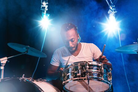Young african-american jazz musician or drummer playing drums on blue studio background in glowing smoke around him. Concept of music, hobby, inspirness. Portrait of joyful attractive artist. 版權商用圖片