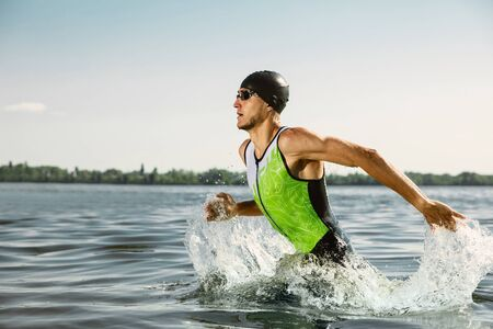 Professional triathlete swimming in rivers open water. Man wearing swim equipment practicing triathlon on the beach in summers day. Concept of healthy lifestyle, sport, action, motion and movement.