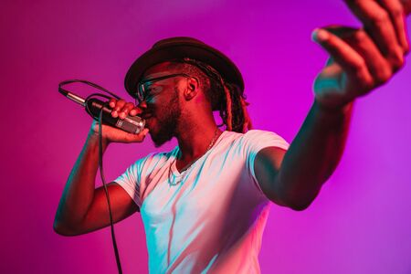 Young african-american jazz musician with microphone singing a song on purple studio background in trendy neon light. Concept of music, hobby, inspirness. Colorful portrait of joyful attractive artist.