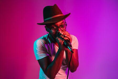 Jonge Afro-Amerikaanse jazzmuzikant met microfoon die een lied zingt op paarse studioachtergrond in trendy neonlicht. Concept van muziek, hobby, inspiratie. Kleurrijk portret van vrolijke aantrekkelijke kunstenaar. Stockfoto